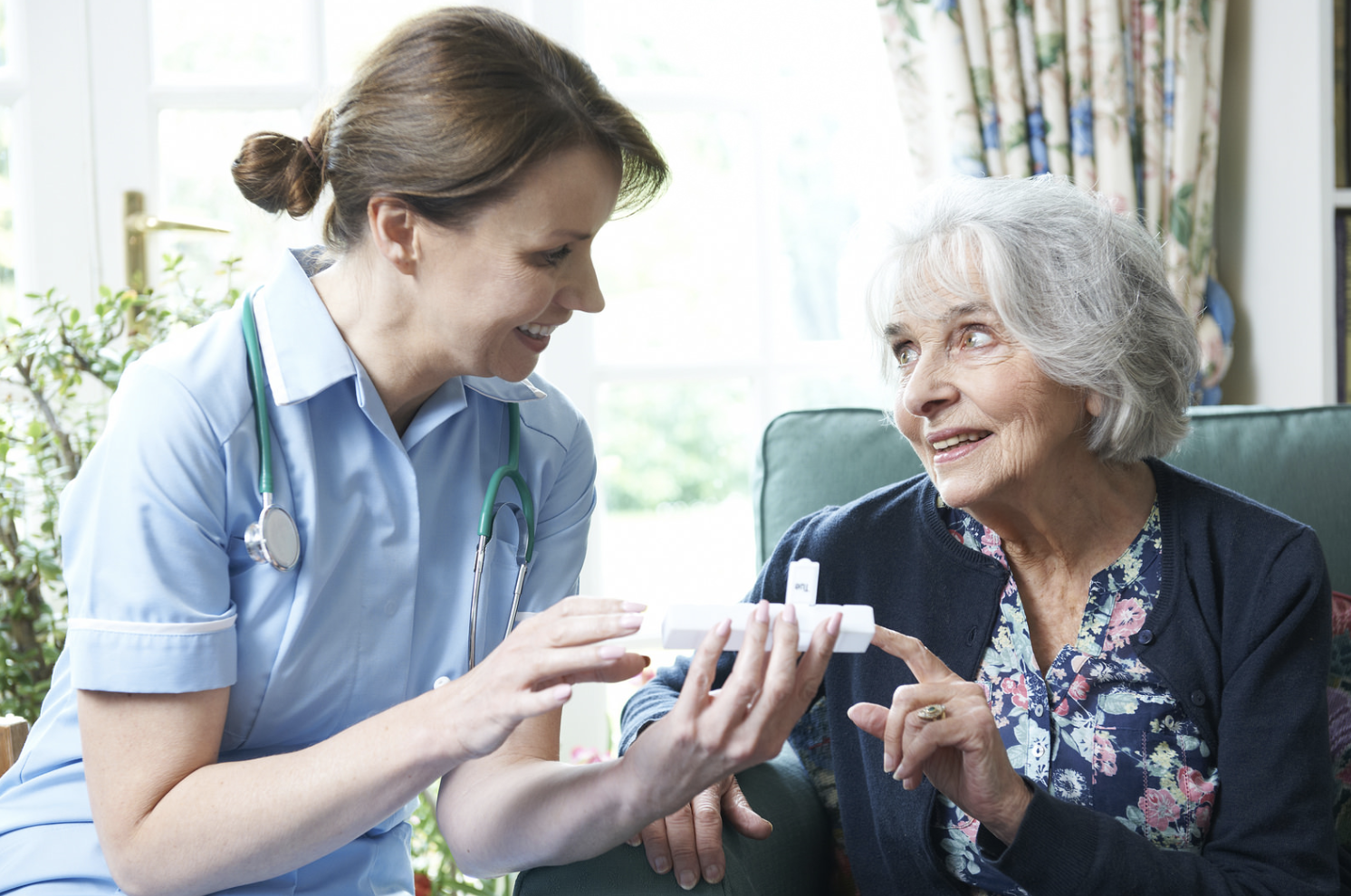 caregiver duties- Caregiver giving medicine to an elderly