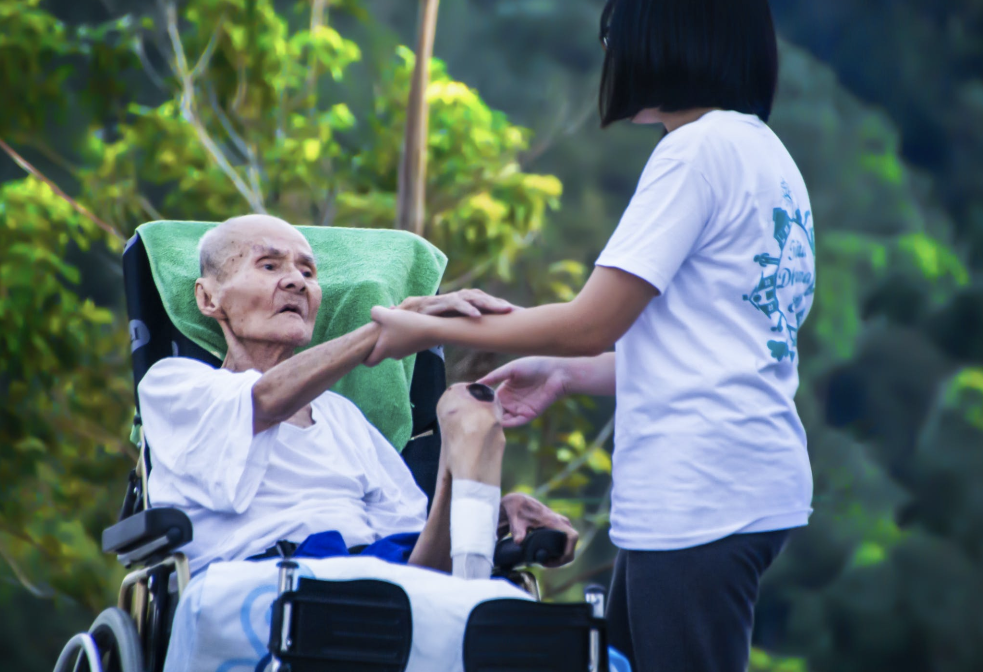 caregiver duties - assisting an elderly in a wheelchair