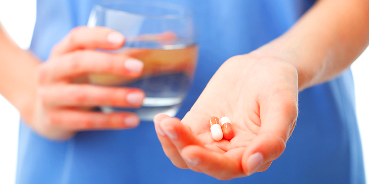 patient holding glass of water and medicine capsules