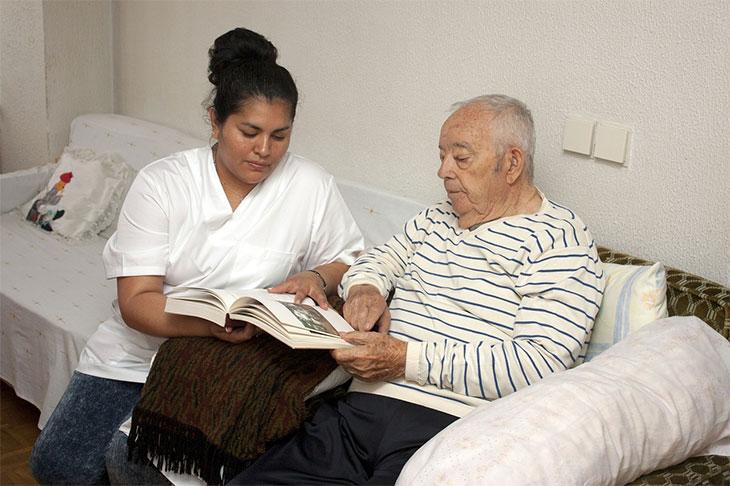 nurse reading to an elderly patient