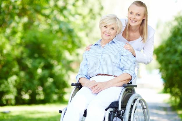 caregiver pushing senior woman wheelchair